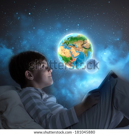 Little cute boy sitting in bed and using tablet. Elements of this image are furnished by NASA - stock photo