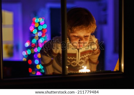 Little cute boy standing by window at Christmas time and blowing candle. With colorful lights from Christmas tree on background, selective focus. - stock photo