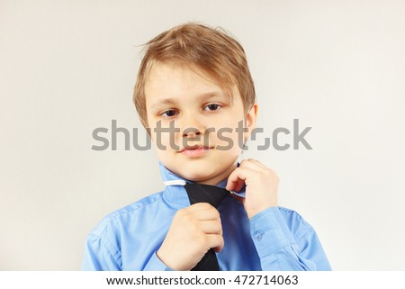 Little cute boy tying his tie over bright shirt