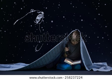 Little cute boy under quilt and his night's reading with torch - stock photo