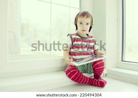Little cute boy using tablet at home having fun time