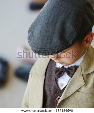 Little cute boy wearing retro suit and hat - stock photo