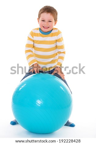 Little cute boy winks, relying on the big blue ball, isolated on white background - stock photo