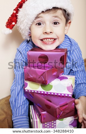 little cute boy with Christmas gifts at home. close up emotional face on boxes in santas red hat. mischief - stock photo