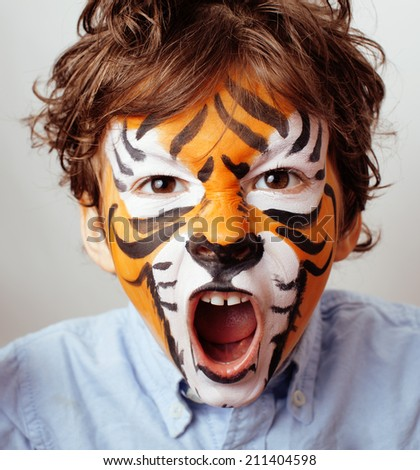 little cute boy with faceart on birthday party close up, little cute tiger - stock photo