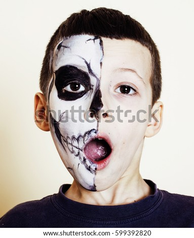 little cute boy with facepaint like skeleton to celebrate hallow