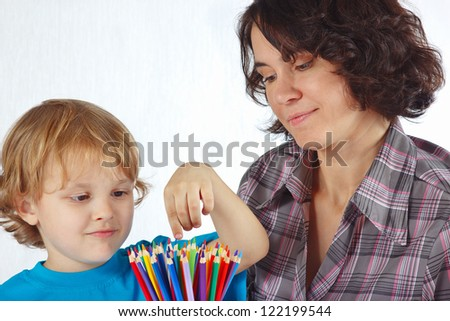 Little cute boy with his mother with color pencils on a white background - stock photo