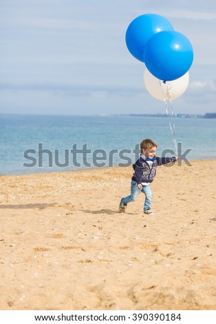 little cute boy with large balloons at the beach
