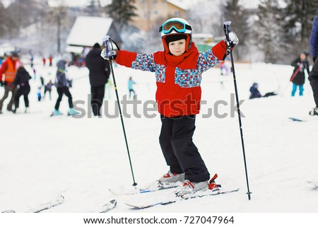 Little cute boy with skis and a ski outfit. Little skier in the ski resort