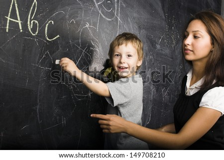 little cute boy with teacher in classroom - stock photo