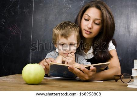 little cute boy with teacher in classroom - stock photo