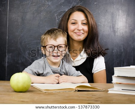 little cute boy with teacher in classroom, siting at table with books and green apple - stock photo