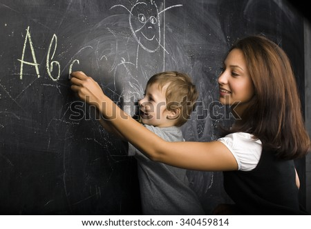 little cute boy with young teacher in classroom studying at blackboard smiling