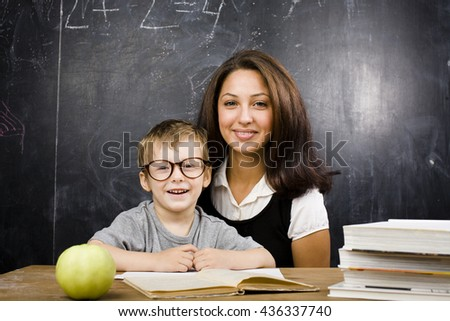little cute boy with young teacher in classroom studying at blackboard smiling - stock photo
