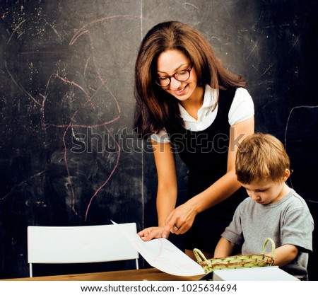 little cute boy with young teacher in classroom studying, lifest