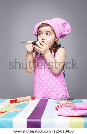 little cute chef tasting her food on grey background - stock photo