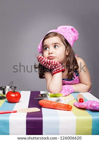 little cute chef thinking about the meal she wants to prepare on grey background - stock photo