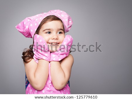 little cute chef wearing pink bib,hat and gloves smiling on grey background - stock photo