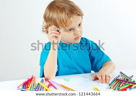 Little cute child draws with color pencils on a white background