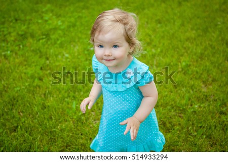 Little cute child girl on a background of green grass