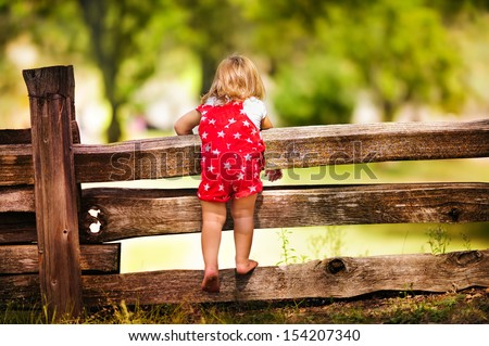 little cute child looking from the wooden fence back view at summer day - stock photo