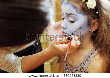 little cute child making facepaint on birthday party, zombie Apocalypse facepainting, halloween preparing