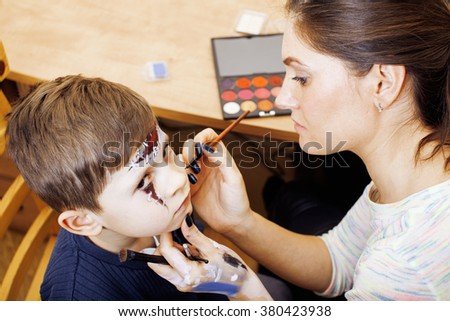 little cute child making facepaint on birthday party, zombie Apocalypse facepainting, halloween preparing - stock photo