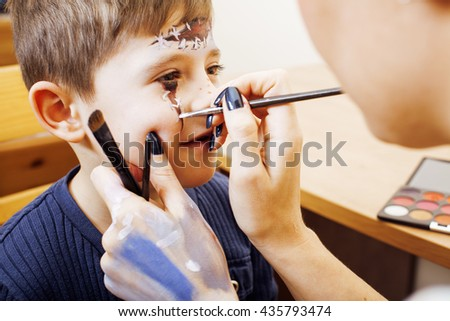 little cute child making facepaint on birthday party, zombie Apocalypse facepainting, halloween preparing concept