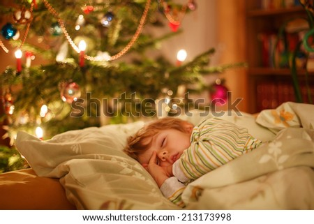 Little cute child sleeping under Christmas tree and dreaming of Santa at home, indoors - stock photo