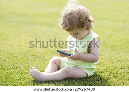 Little cute curious baby boy with blond curly hair in light summer clothes sitting on lawn with fresh green grass sunny day outdoor holding mobile phone, horizontal picture - stock photo