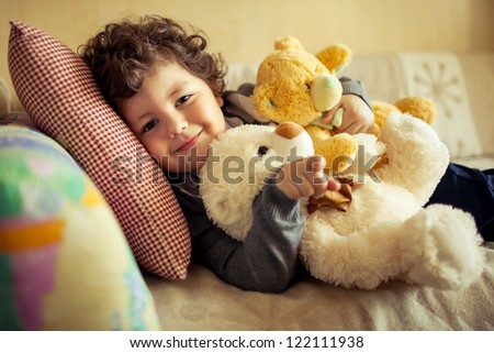 little cute curly  boy laying at couch with teddy bear - stock photo