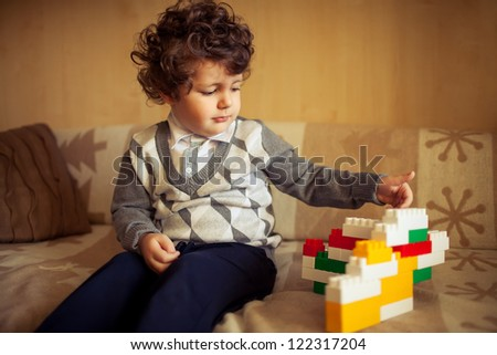little cute curly  boy sitting at couch with constructor - stock photo