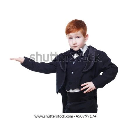 Little cute funny redhead boy in tailcoat tuxedo show something pointing at nowhere. Portrait of well-dressed child in bow tie isolated on white background - stock photo