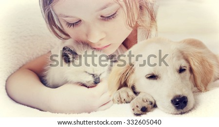 little cute girl affectionately hugging  kitten and Puppy