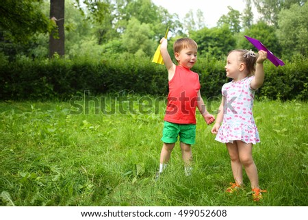 Little cute girl and boy play with paper airplanes in summer park