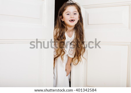 little cute girl at home, opening door well-dressed in white dress, adorable milk fairy teeth - stock photo