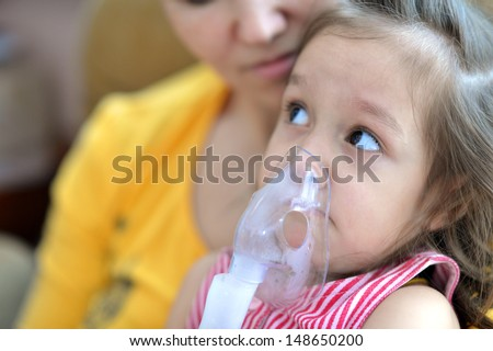 little cute girl doing inhalation at home - stock photo