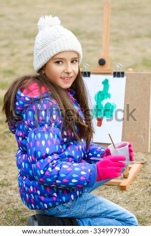 little cute girl draws paints on an easel outdoors - stock photo