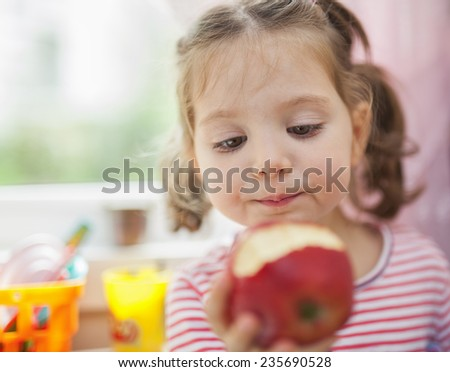little cute girl eating red apple - stock photo