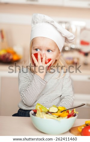 Little cute girl eating tomato while cooking salad. Kitchen interior. Concept for young kitchen hands - stock photo