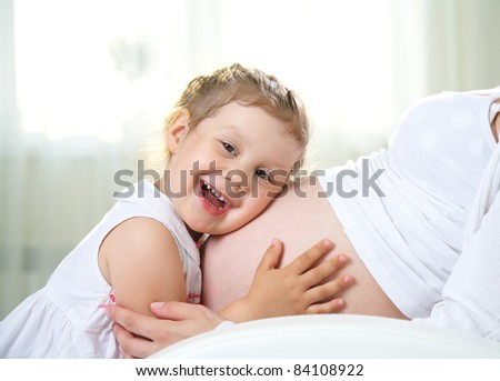 Little cute girl embracing her pregnant mother