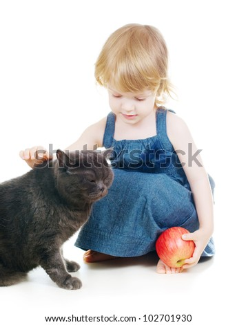 Little cute girl feeding cat with an apple - stock photo