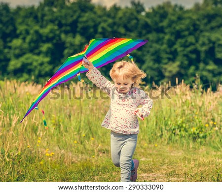 little cute girl flying a kite in a meadow on a sunny day. close-up - stock photo