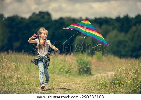 little cute girl flying a rainbow kite in a meadow on a sunny day - stock photo