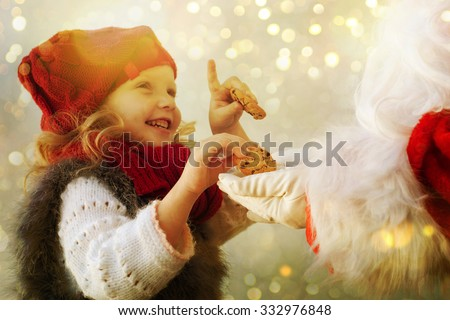 Little cute girl giving cookies to Santa Claus  - stock photo