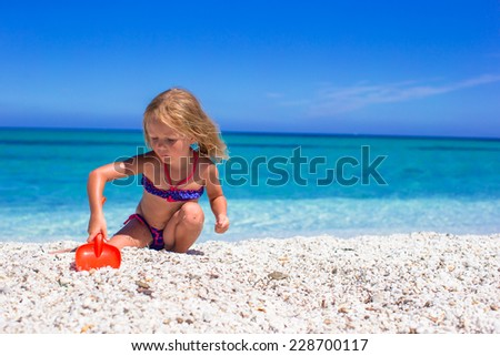 Little cute girl have fun with beach toys at tropical beach