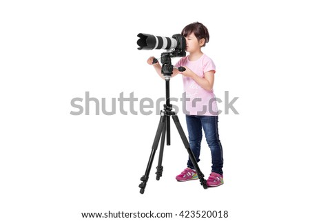 little cute girl holding a digital  professional photo camera on tripod. child photographs