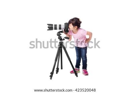 little cute girl holding a digital  professional photo camera on tripod. child photographs - stock photo