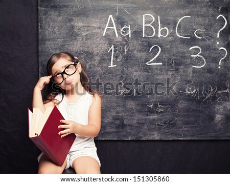 little cute girl holding a red book thinking in front of a blackboard - stock photo