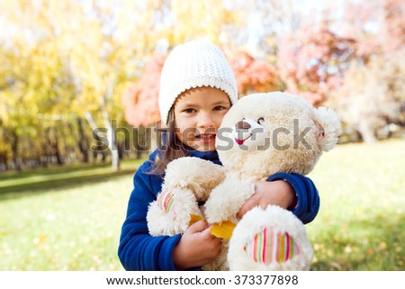 Little cute girl holding large teddy bear - stock photo